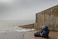 Pictured: A drone is seen in the distance near an RNLI rescuer poses as a casualty on a slipway in on a beach St Donats, Wales, UK. Friday 20 April 2018 <br /> Re: The Royal National Lifeboat Institution (RNLI) and the Maritime and Coastguard Agency (MCA) have held a special media event to demonstrate how drones could be used in search and rescue activity in the future to help save lives at the Atlantic College in St Donats, south Wales, UK. <br /> The rescue scenario took place along a stretch of coastline in south Wales, featuring a drone, an RNLI lifeboat and an MCA helicopter winching the casualty to safety.