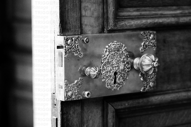 An ornate period metal door handle with lock
