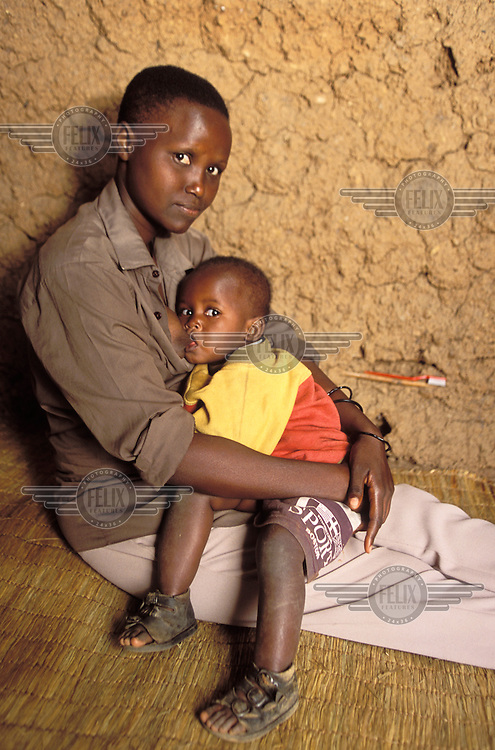 22 year old Honorine Tuyiseng breastfeeds her son Umunezero. Honorine was beaten and raped during the genocide and now lives at a relative's house with her child.