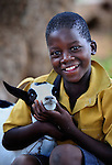 "A boy and his family's goat in Chisatha, a village in southern Malawi. His community has been hard hit by drought in recent years, leading to chronic food insecurity, especially during the ""hunger season,"" when farmers are waiting for the harvest. The ACT Alliance is working with farmers in this village to switch to alternative, drought-resistant crops, such as millet, as well as using irrigation and other improved techniques to increase agricultural yields. Solar panels will power a pump that will draw water from a river into a reservoir and then into six elevated 5,000 liter tanks, which will then provide water to grow healthy crops year round. And the ACT Alliance is distributing goats, including this one, for families to raise."