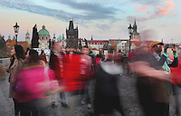 Tourists crossing the Charles Bridge or Karluv most, built 1357 - 15th century, looking towards the Old Town bridge tower, across the Vltava river in Prague, Czech Republic. Its construction began under King Charles IV, replacing the old Judith Bridge built 1158'??1172 after flood damage in 1342. This new bridge was originally called the Stone Bridge (Kamenny most) or the Prague Bridge (Prazsky most) but has been the Charles Bridge since 1870. The bridge is 621m long and nearly 10m wide, resting on 16 arches shielded by ice guards. It is protected by three bridge towers, two on the Lesser Quarter side and one in Gothic style on the Old Town side. The historic centre of Prague was declared a UNESCO World Heritage Site in 1992. Picture by Manuel Cohen