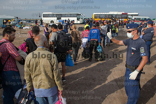 Police officers stand guard as illegal migrants get on buses after crossing the border between Serbia and Hungary near Roszke (about 174 km South of capital city Budapest), Hungary on September 14, 2015. ATTILA VOLGYI