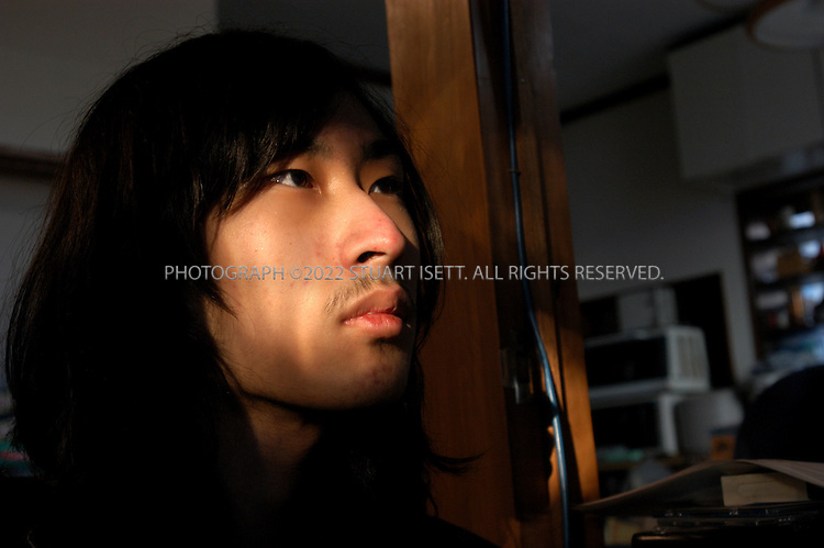 11/29/2002--Shiki City,  Japan..A beam on sunlight strikes the face of 19 year old Dai Hasebe at 'Ayutaka', a free space created by Nobuyuki Minami for children who are bullied in school or are shut-ins. Dai has been a 'hikikomori', or shut-in, since he was 11, rarely venturing out of his family's apartment, instead spending all his time shut off from the world in the tiny apartment. Dai makes models to help keep himself busy..Experts estimate that at up to a million Japanese live as shut-ins as they hide from the social pressures of Japanese society...All photographs ©2003 Stuart Isett.All rights reserved.This image may not be reproduced without expressed written permission from Stuart Isett.