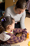 Educaton preschool 4-5 year olds visiting psychologist working with girl at table card stringing activity vertical