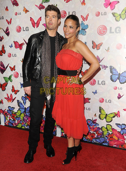 ROBIN THICKE & PAULA PATTON.The LG Rumorous Night, an exclusive party to celebrate style and introduce the personalized LG Rumor2 backplate designed by fashion icon Heidi Klum held at The Andaz Hotel in West Hollywood, California, USA..April 29th, 2009.full length black leather jacket red dress strapless open toe ankle boots clutch bag scarf jeans denim married husband wife hand on hip .CAP/DVS.©Debbie VanStory/Capital Pictures.