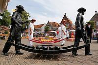 Kaasdragers op de Kaasmarkt in Edam. Bronzen beeldengroep bij de Waag