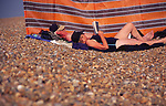 AJDNE8 Elderly couple sunbathing by windbreak Shingle Street Suffolk England