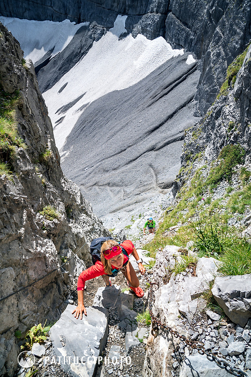 Climbing a steep trail section with chains, Dent du Midi, Switzerland