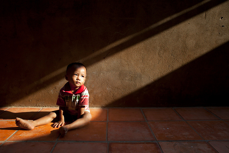 A toddler sits in a shaft of light in a village outside of Phnom Penh, Cambodia. <br /> <br /> Photos &copy; Dennis Drenner 2013.