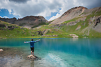 Female hiker balances on rock in Ice Lake, Ice Lakes basin, San Juan mountains, Colorado, USA