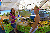 Young women holding fresh, cold coconuts at a North Shore fruit stand in Haleiwa