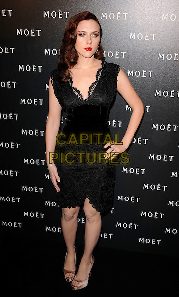 SCARLETT JOHANSSON.Moet & Chandon hosts a Tribute to Cinema at Big Sky Studios, Brewerey Road, London, England..March 25th, 2009.full length black lace trim dress waistband gold beige silk satin platform peep toe shoes heels christian louboutin  hand on hip sleeveless .CAP/CAN.©Can Nguyen/Capital Pictures.