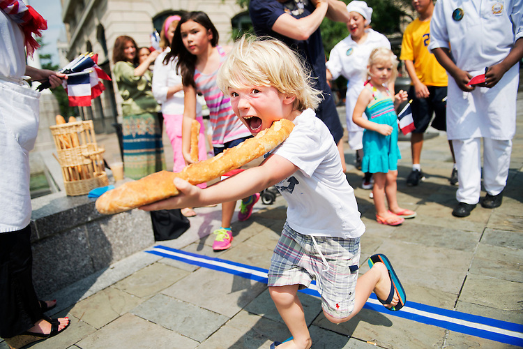UNITED STATES - JULY 14: Winston West, 5, of the District, participates in the 4th Annual Bastille Day Baguette Relay Race at the Navy Memorial which was hosted by Paul Bakery & Cafe, July 14, 2014. (Photo By Tom Williams/CQ Roll Call)