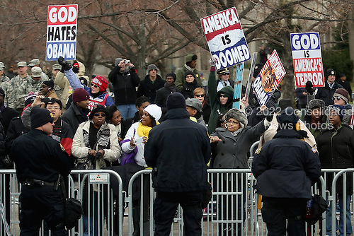 Demonstrators from the Westboro Baptist Church hold up signs along the Inaugural Parade route as United States President Barack Obama's motorcade travels from the White House to the U.S. Capitol along Pennsylvania Avenue January 21, 2013 in Washington, DC. Obama and U.S. Vice President Joe Biden will begin their second term in office by taking the Oath of Office later in the morning during a ceremony on the West Front of the U.S. Capitol.  .Credit: Chip Somodevilla / Pool via CNP