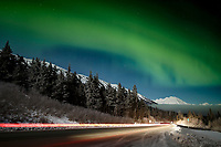 winter landscape shows Northern Lights (Aurora Borealis) in sky above Kenai Mountains inTurnagain Pass area with car lights on Seward Highway    January 2014