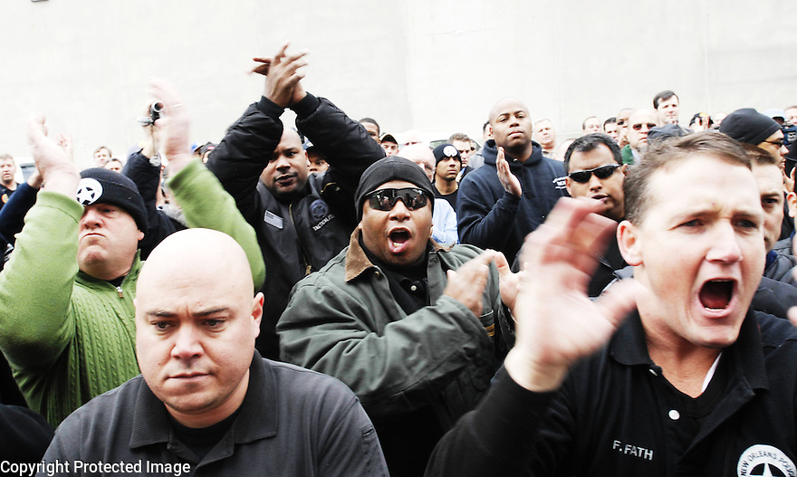 "Police officers and fellow supporters chant ""NOPD"" and applaud as seven New Orleans police officers turn themselves in at the city jail in New Orleans Tuesday, Jan. 2, 2007. Seven officers have been charged in connection with deadly shootings at the Danziger Bridge during the aftermath of Hurricane Katrina..(AP Photo/Cheryl Gerber)."