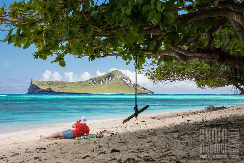 A man looks out towards Rabbit (or Manana) Island at Waimanalo Beach, Windward O'ahu.