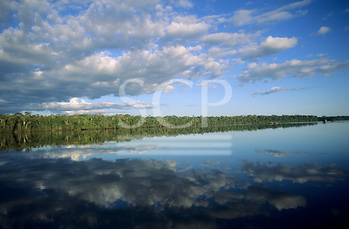 Mato Grosso State, Amazon, Brazil. Forested river bank with perfect reflection of sky with scudding clouds and trees in the river.