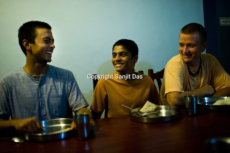 """Devotees share a lighter moment on the dining table during dinner at the Kaliya Mardana Krishna Ashram in the coastal town of Mulki, just north of Mangalore, Karnataka, India.  ..Krishna devotees in the Gaudiya Vaishnava tradition of Hinduism, they are known collectively as the """"surfing swamis."""" The """"surfing ashram"""" is growing in popularity and surfing here is a form of meditation, a spiritual practice leading to heightened states of awareness."""