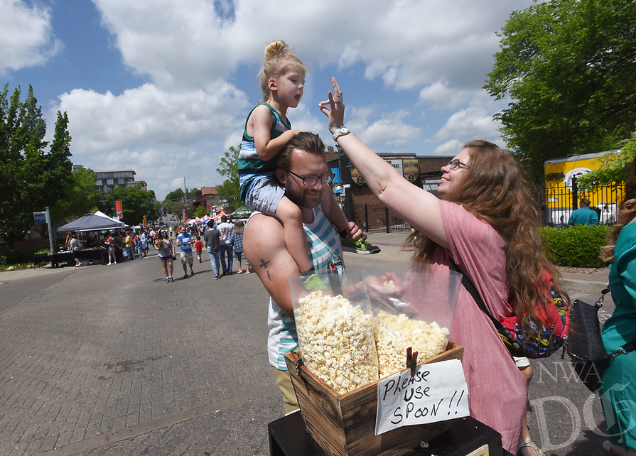 NWA Democrat-Gazette/FLIP PUTTHOFF <br /> SPRINGFEST TREATS<br /> Tasha Finkus helps her daughter, Kai Finkus, 3, sample free popcorn on Saturday April 15 2017 during Springfest on Dickson Street in Fayetteville. Kai is on the shoulders of her dad, Jacob Finkus. The annual event featured bed races, a pet parade, 5-kilometer run, pancake breakfast, vendor booths and music. Springfest was started in 1983 by Dickson Street merchants to celebrate the history, culture and flavor of Fayetteville.
