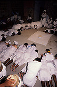 Recife, Pernambuco State, Brazil. Candomble religion: healing ceremony; people in white in circle around food offering.