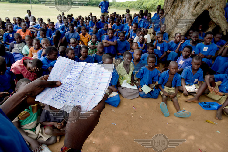 Students gather under a tree to listen to the Health Prefect speak about general hygiene and sanitation issues, as well as menstrual hygiene, at Aputiri Primary School.