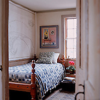 A large map of the coast of Cape Cod covers and entire wall of this small bedroom