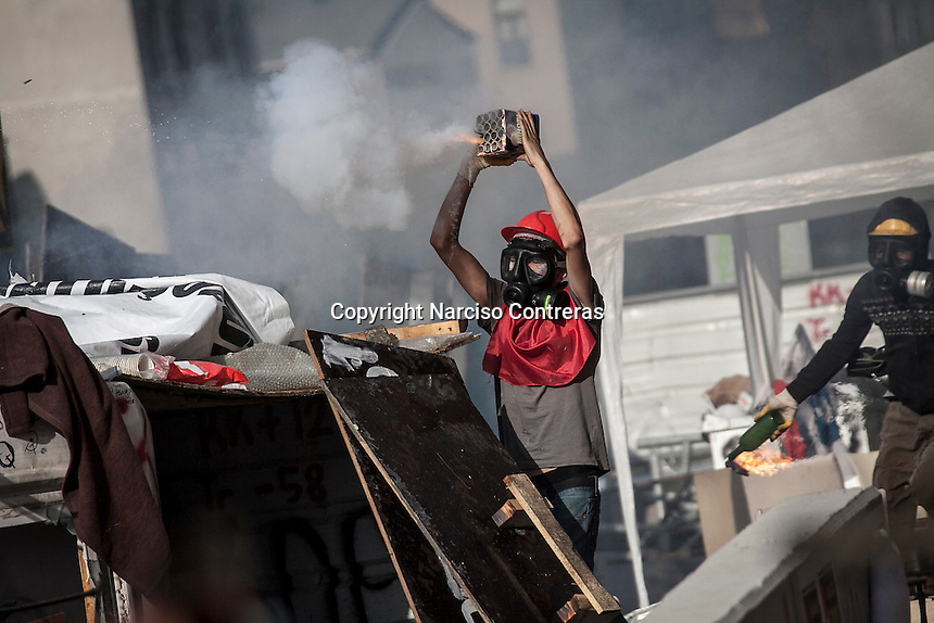 In this Tusday, Jun. 11, 2013 photo, a protester aims to the anti-riot police with fireworks duriing clashes at the streets of Taksim Square in Istanbul,Turkey. (Photo/Narciso Contreras).