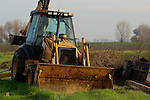 Tractor bulldozer backhoe digger in field, Merced County, Central Valley, California