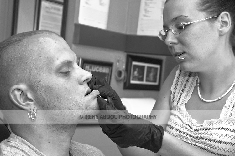 Sean Jeweii, a body piercer in Rockland Maine, gives his apprentice, Tracy Baker, some practice by allowing her to pierce his chin.