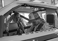 Marty Robbins, left, helps Darrell Waltrip strap into Robbins' car for a shakedown run before the Firecracker 400 Daytona International Speedway Daytona Beach FL July 1982.(Photo by Brian Cleary/www.bcpix.com)(Photo by Brian Cleary/www.bcpix.com)