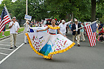 Wantagh, New York, USA. July 4, 2015. An Ecuadorian women fans out her colorful traditional dress as she leads The Ecuadorian Community marchers in the Wantagh Independence Day Parade, a long-time July 4th tradition on Long Island.