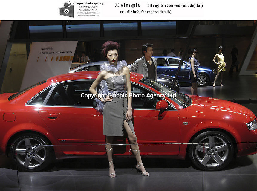 Chinese models pose besides Audi cars at the Auto China 2004 exhibition in Beijing, China..