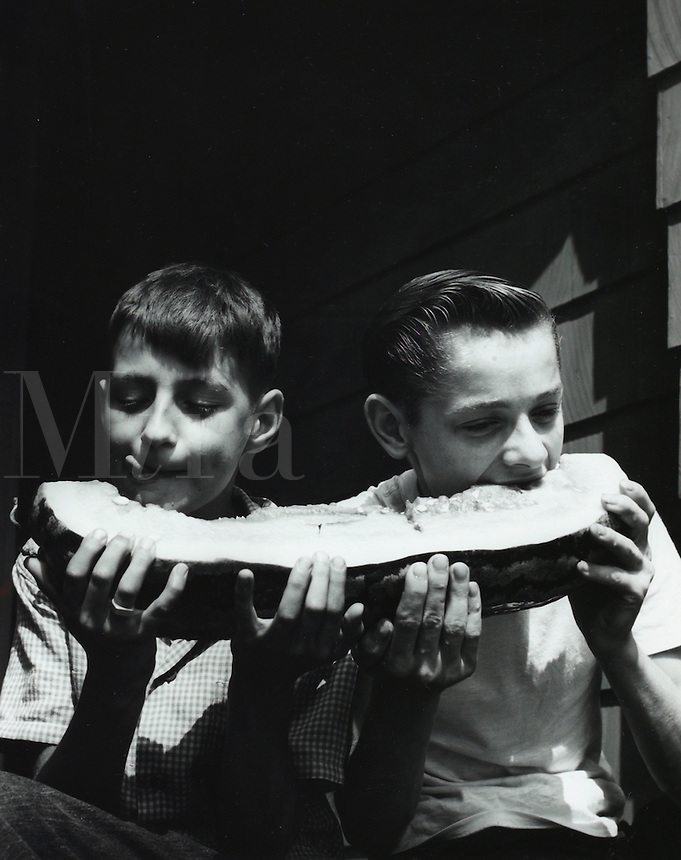 Two boys sharing a watermelon. 1950's.
