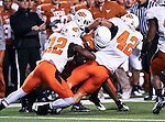 Oklahoma State Cowboys safety Johnny Thomas (12) and Oklahoma State Cowboys linebacker Justin Gent (42) tackle Texas Longhorns wide receiver Malcolm Williams (9) during the game between the Oklahoma State Cowboys and the University of Texas in Austin Texas Longhorns at the Daryl K. Royal- Texas Memorial Stadium in Austin, Texas. The Oklahoma State Cowboys defeated the Texas Longhorns 33 to 16.