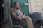 Africa, Tunisia, Tozeur. Grim looking local tunisian man sitting in front of a tyre shop in Tozeur's old quarter. --- No releases available, but releases may not be needed for certain uses. --- Info: Tozeur, and the Jerid region, is very famous for its yellow/brownish brick architecture as well as its fascinating patterns in simple and rich geometric designs form the façades of most buildings in the old city/medina. --- Info: Image belongs to a series of photographs taken on a journey to southern Tunisia in North Africa in October 2010. The trip was undertaken by 10 people driving 5 historic Series Land Rover vehicles from the 1960's and 1970's. Most of the journey's time was spent in the Sahara desert, especially in the area around Douz, Tembaine, Ksar Ghilane on the eastern edge of the Grand Erg Oriental.