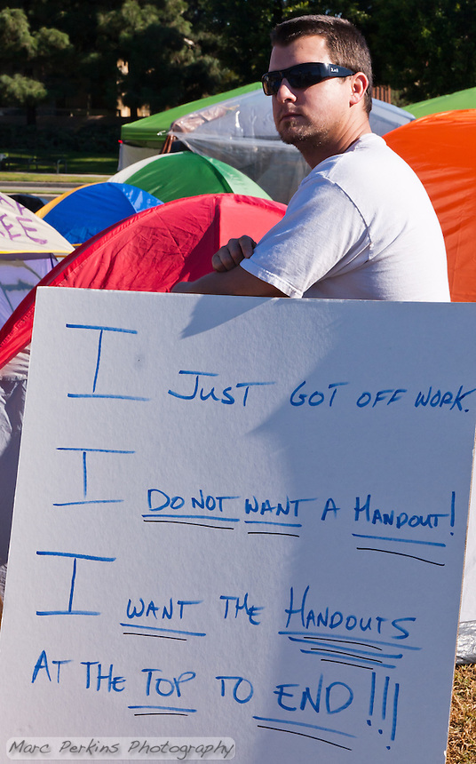 """Luke, who as his sign says had just gotten finished with his job as a machinist for the day, stands among the tents at the Irvine Occupy Orange County camp.  His sign reads, """"I just got off work.  I do not want a handout!  I want the handouts at the top to end!!!""""."""