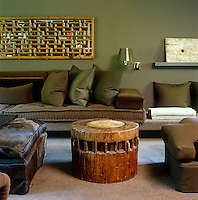 In this living room the oversize sofa has been upholstered in luxurious dark brown alpaca and different textures of brown and green have been used throughout the room