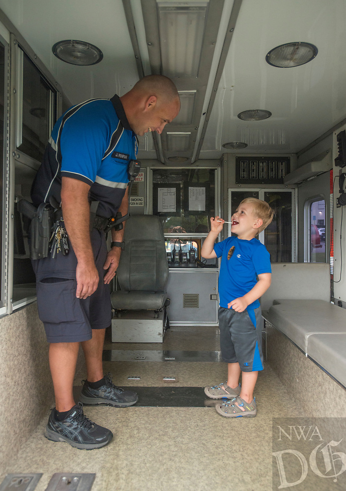 NWA Democrat-Gazette/BEN GOFF @NWABENGOFF<br /> Levi King, 3, of Springdale takes a look inside the the Springdale Police Department's negotiator vehicle with officer Jason Renfrow Tuesday, Aug. 7, 2018, during the Springdale Police Department's National Night Out event at Murphy Park. The annual campaign aims to build police-community relationships and promote safer neighborhoods with games and activities for children and ways for families to interact with police in a casual setting.