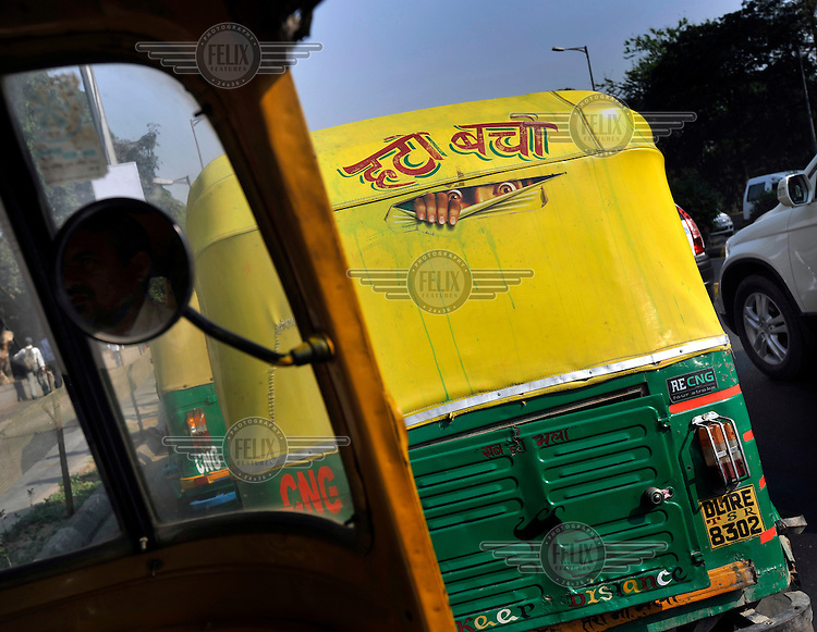 Artwork on the back of an auto rickshaw in a traffic jam.