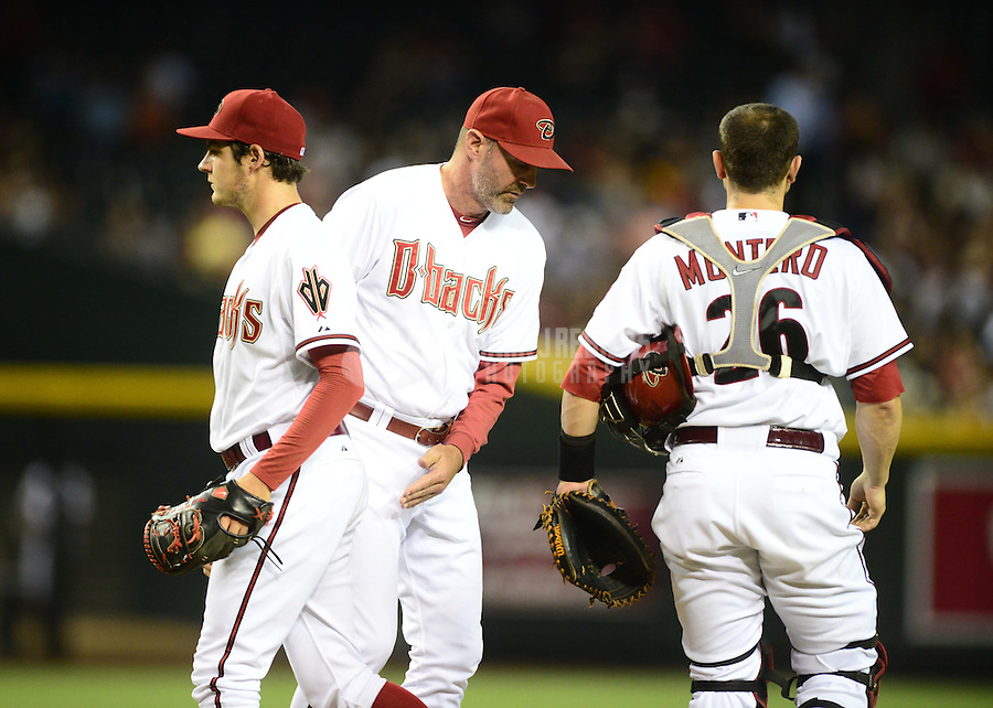 Jul. 3, 2012; Phoenix, AZ, USA: Arizona Diamondbacks pitcher Trevor Bauer (left) walks off the mound after giving the ball to manager Kirk Gibson (center) as catcher Miguel Montero looks on against the San Diego Padres at Chase Field. Mandatory Credit: Mark J. Rebilas-