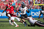 Reggie Gallaspy II (25) of the North Carolina State Wolfpack is dragged down by his jersey by Dante Sawyer (95) of the South Carolina Gamecocks during second half action in the Belk College Kickoff at Bank of America Stadium on September 2, 2017 in Charlotte, North Carolina.  The Gamecocks defeated the Wolfpack 35-28.  (Brian Westerholt/Four Seam Images)