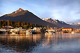 USA, Alaska, Sitka, a peaceful view of homes and fishing boats along the shore in Sitka Harbor at sunset, Crescent Bay