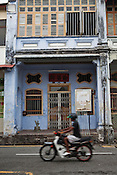A motorist rides past the restored heritage houses in the UNESCO heritage town - Georgetown of Penang, Malaysia. Photo: Sanjit Das/Panos