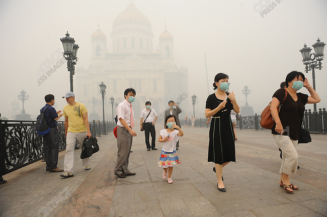 In central Moscow by the cathedral of Christ the Saviour a thick stinging smog enveloped the city and many, including these foreign tourists, donned masks to escape its effects as the hot weather and the forest and turf fires outside the capital showed little sign of abating. 06 August 2010