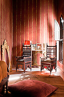 The walls of one of the bedrooms of The Red Apartment have been painted a deep terracotta red with gold stripes
