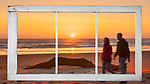 Viewed out a vintage window, couple walks the beach at Cape Disappointment State Park, Washington, at sunset.