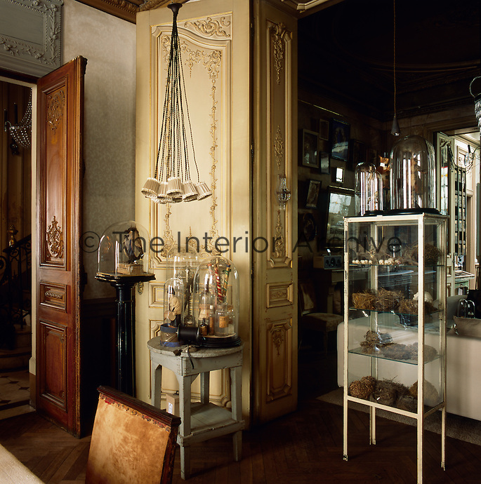 An eclectic mix of various items are displayed under glass domes and in a glass display cabinet in a traditional room.