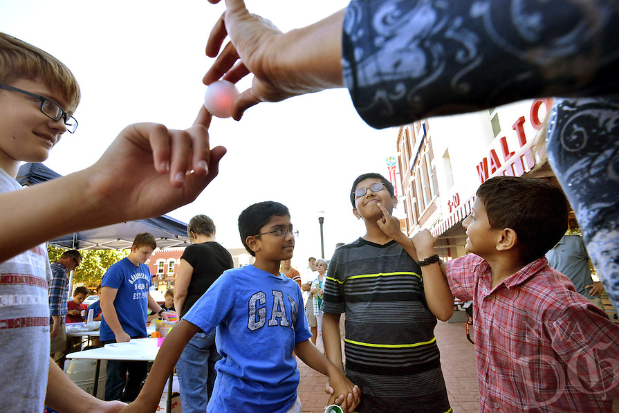 STAFF PHOTO BEN GOFF  @NWABenGoff -- 09/21/14 <br /> Ronak Pai, 7, from right, tries to deliver a mild shock to his brother Nikhil Pai, 11, while holding hands to complete an electrical circuit with Rishi Leburu, 9, and Jack Charlson, 12, all of Bentonville, while participating in The Walmart Museum's Sidewalk Sundays with IBM in downtown Bentonville on Sunday September 21, 2014. The Science Technology Engineering and Mathematics-themed event is part of IBM month at the Walmart Museum, which will continue with a second Sidewalk Sunday next week, and included activities such as making your own ice cream with liquid nitrogen, cotton ball catapults and paper gliders.