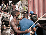 A fight breaks out over the goods in an overturned truck on the side of the road between Port-au-Prince and Les Cayes.